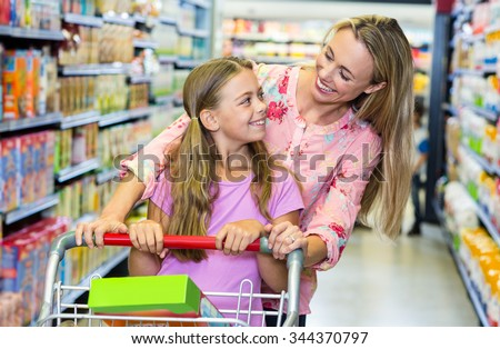 Smiling mother and daughter at the supermarket - stock photo