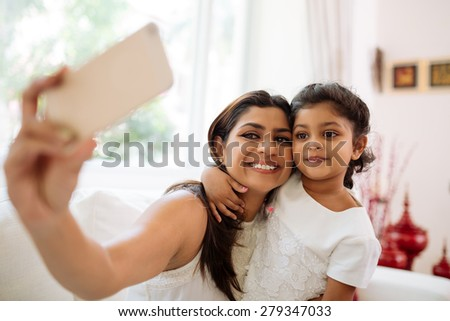 Smiling mother and daughter bonding together to take a selfie - stock photo