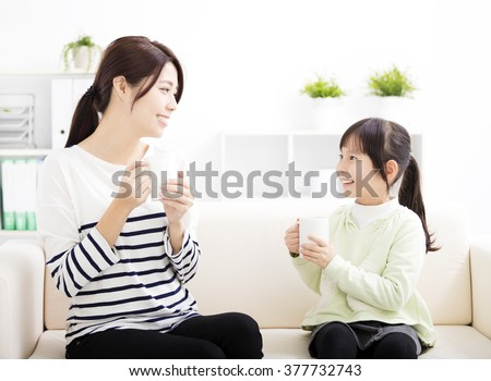 smiling mother and daughter on the sofa - stock photo