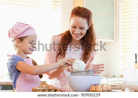 Smiling mother and daughter preparing dough together - stock photo