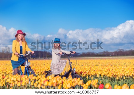 Smiling mother and daughter riding bikes through beautiful blooming tulip fields at the daylight - stock photo