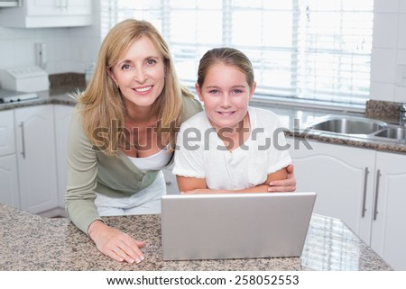 Smiling mother and daughter using laptop together at home in the kitchen - stock photo