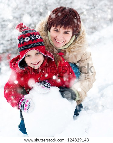 Smiling mother and daughter with snowman - stock photo