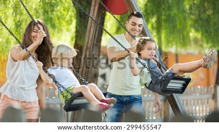 Smiling  mother and father swinging children at park. Focus on woman - stock photo