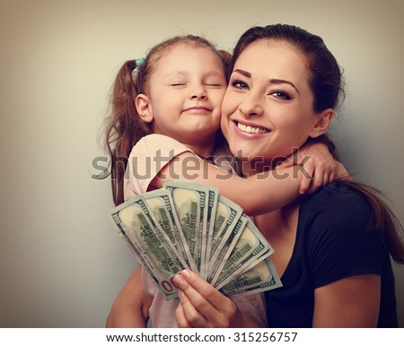 Smiling mother and happy cute daughter cuddling and showing dollars. Happy winning family. Vintage closeup portrait - stock photo
