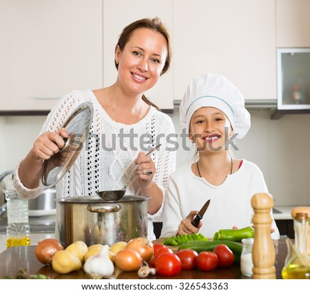 Smiling mother and her cheerful daughter in cookersâ??s hat preparing soup together - stock photo
