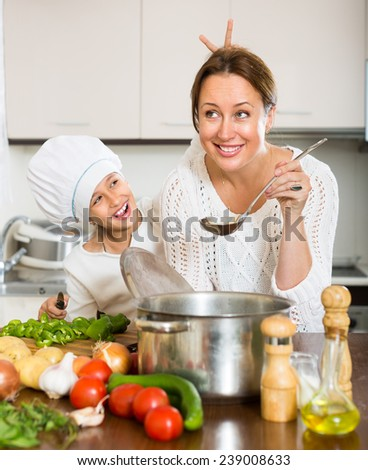 Smiling mother and her cheerful daughter preparing soup at domestic kitchen. Focus on woman  - stock photo