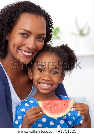 Smiling mother and her daughter eating fruit at home - stock photo