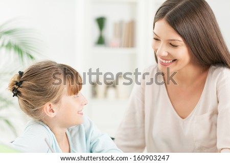 Smiling mother and her daughter looking lovingly at each other. - stock photo