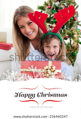Smiling mother and her daughter opening Christmas gifts against border - stock photo