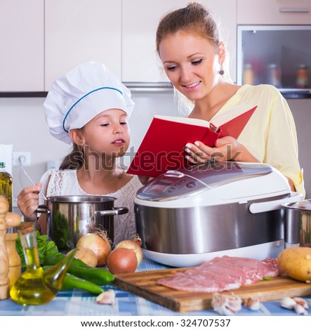 Smiling mother and little child preparing meat in slow-cooker - stock photo