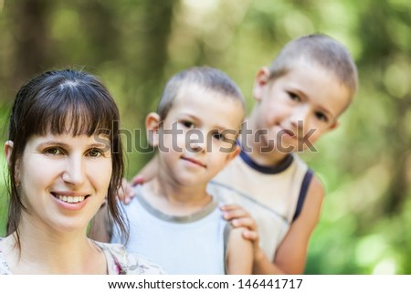 Smiling mother and little sons walking outdoor in family happiness - stock photo