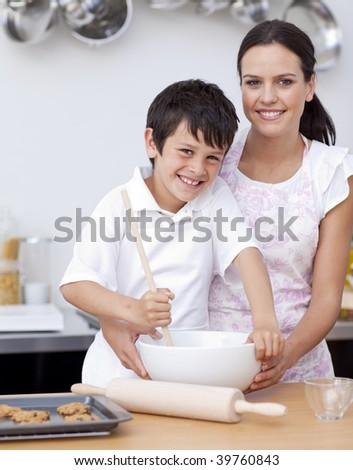Smiling mother and son having fun in the kitchen - stock photo