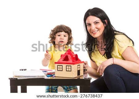 Smiling mother and son sitting at table and doing educational activity together - stock photo
