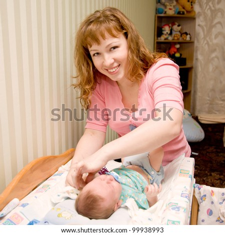Smiling mother cares newborn baby - stock photo