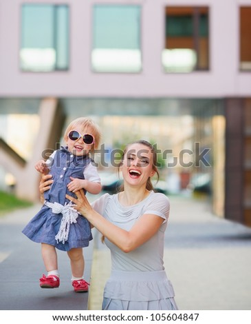 Smiling mother playing with baby in city - stock photo