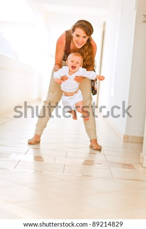 Smiling mother playing with her adorable baby - stock photo