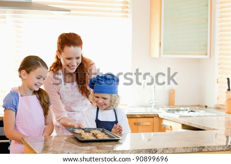 Smiling mother presenting finished cookies to her children - stock photo
