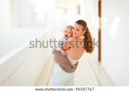 Smiling mother with baby playing outdoor - stock photo