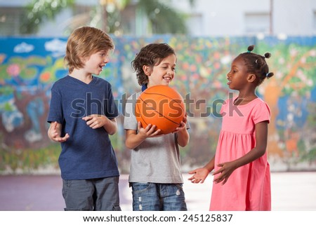 Smiling multi ethnic kids playing in schoolyard. - stock photo