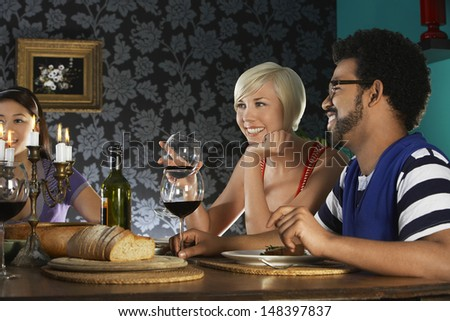 Smiling multiethnic friends enjoying dinner party - stock photo