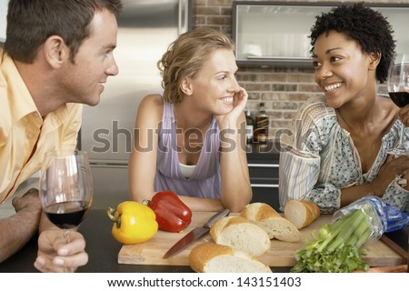 Smiling multiethnic friends preparing food at kitchen counter - stock photo