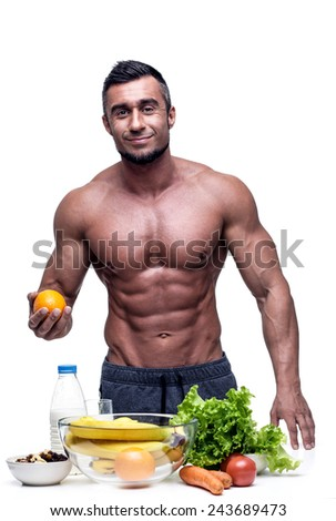 Smiling muscular man standing with vegeterian food - stock photo