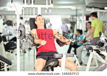Smiling muscular young man exercising in a fitness club - stock photo