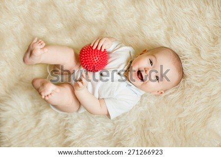 smiling newborn baby boy playing with a red ball - stock photo