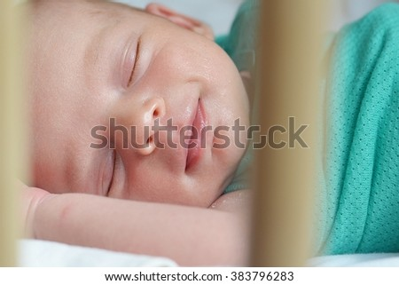 Smiling newborn baby sleeping in a cot - stock photo