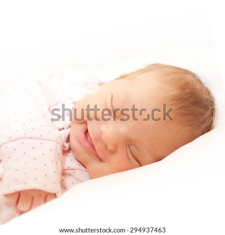 Smiling newborn baby sleeping on a white bed. Isolated on white background. - stock photo