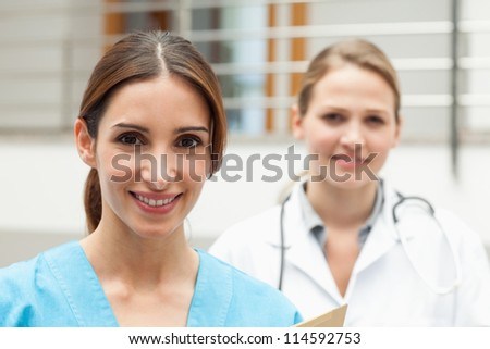 Smiling nurse and doctor standing in a hospital reception - stock photo