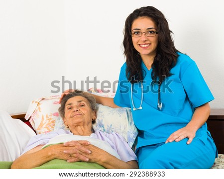 Smiling nurse caring for kind elder patient in nursing home. - stock photo