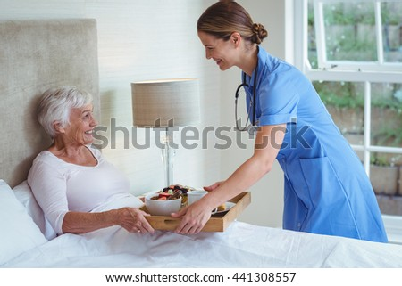 Smiling nurse giving food to senior woman at home - stock photo