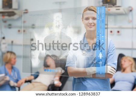 Smiling nurse standing behind blue display screen showing x-ray - stock photo