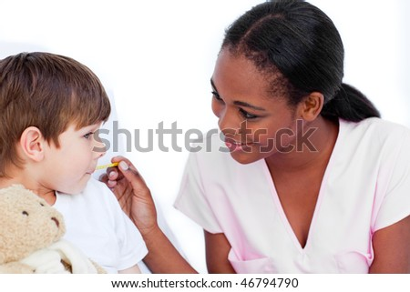 Smiling nurse taking little boy's temperature in a hospital - stock photo