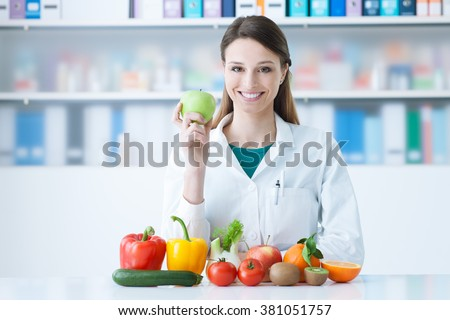 Smiling nutritionist in her office, she is holding a green apple and showing healthy vegetables and fruits, healthcare and diet concept - stock photo
