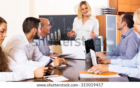 Smiling office staff gathered in the modern conference hall for the meeting - stock photo