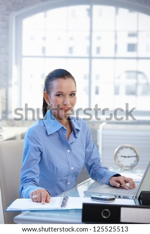 Smiling office worker girl busy at desk with laptop computer and documents. - stock photo