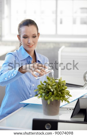 Smiling office worker girl watering potted plant, sitting at desk.? - stock photo