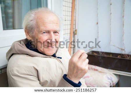 smiling old man holding a cigarette, its a bad habit, but he is enjoying it - stock photo