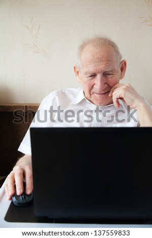 smiling old man holding computer mouse - he is working on a laptop - stock photo