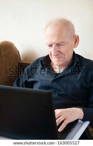 smiling old man in a black shirt is working on a laptop - stock photo