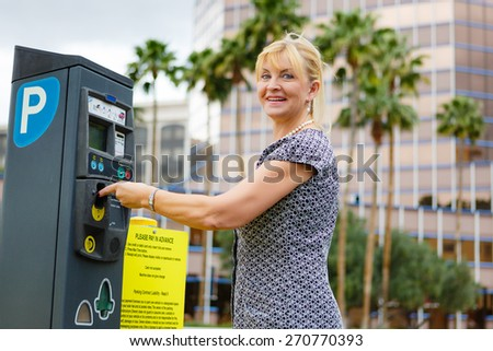 Smiling Old senior woman 60-65 years paying for parking in the street - stock photo