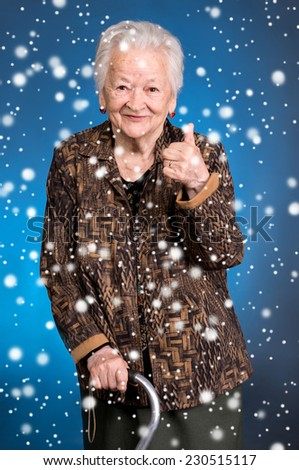 Smiling old woman standing with a cane and showing ok . Christmas and holidays concept - stock photo