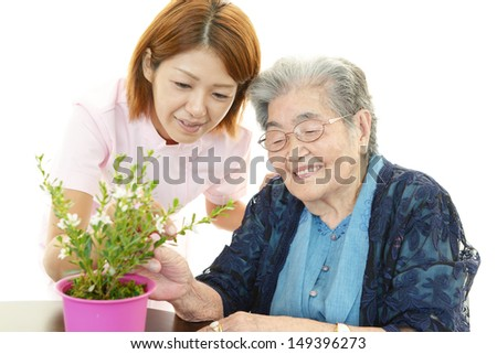 Smiling old woman with plant - stock photo