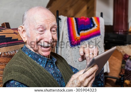 Smiling older gentleman working on a tablet in his living-room - stock photo