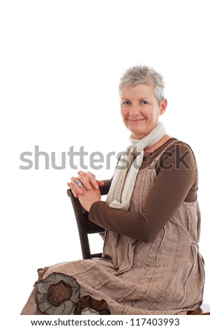 Smiling older woman sits sideways on chair. She wears flowered boots and brown cotton shift dress. Closeup, isolated on white background, vertical, copy space. - stock photo