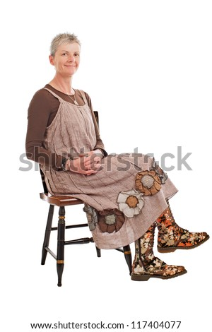 Smiling older woman with short gray hair sits sideways on chair, hands clasped. She wears flowered boots and brown cotton shift dress. Isolated on white background, vertical, copy space. - stock photo