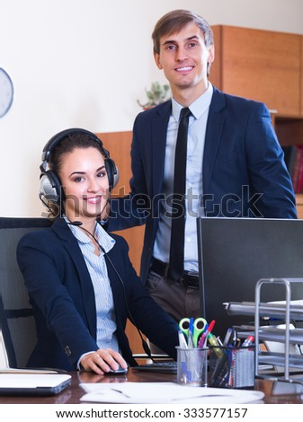 Smiling operators of customer support working in call centre. Focus on woman